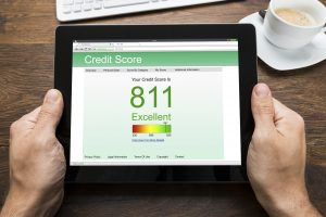 Close-up Of Person Hands With Digital Tablet Showing Credit Score At Desk